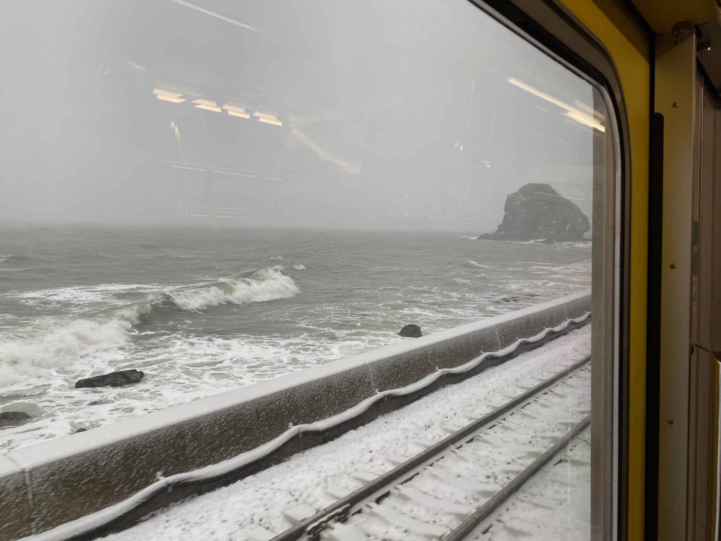 Photo of snow by the sea waves from a train
