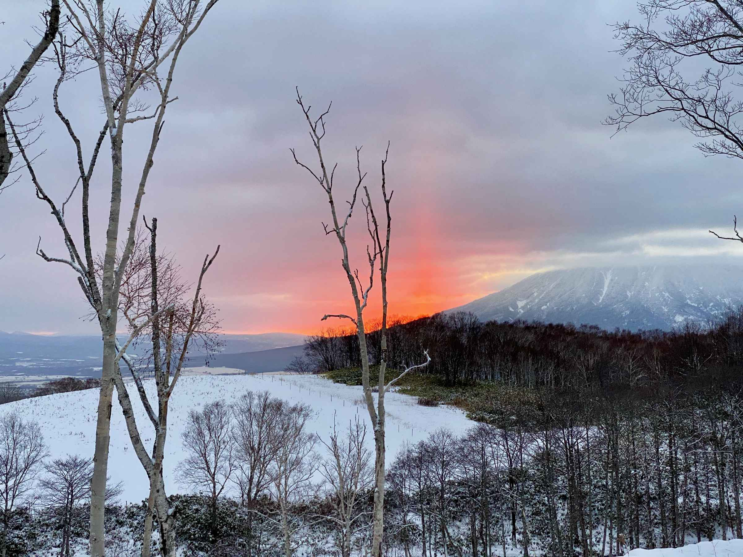 Photo of the sun rising from behind a nearby mountain